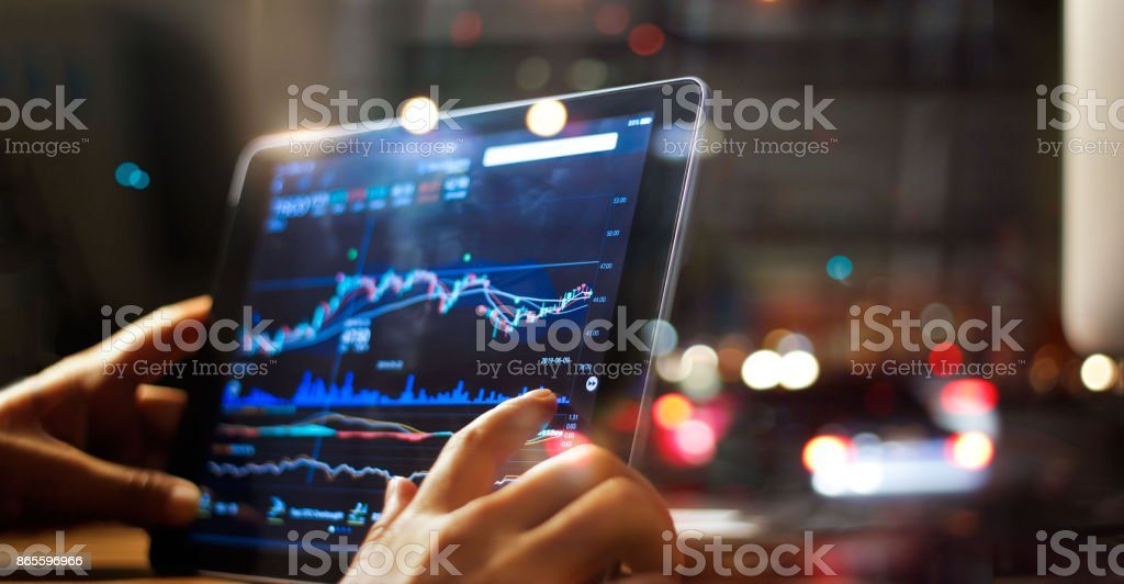 Businessman checking stock market data on tablet on night background stock photo