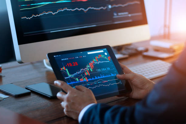 Businessman checking stock market on digital tablet and a desktop computer with stock exchange graph on screen. Financial stock market. Analyzing data in office background. Businessman checking stock market on digital tablet and a desktop computer with stock exchange graph on screen. Financial stock market. Analyzing data in office background. stock market stock pictures, royalty-free photos & images