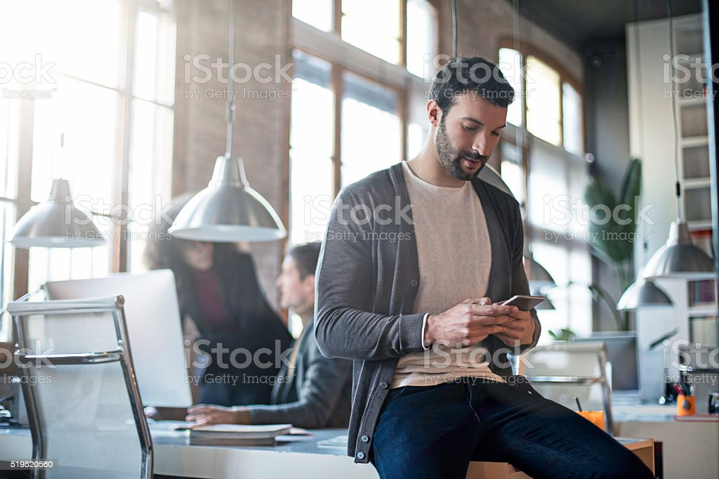 Businessman checking the mobile phone sitting on his desk stock photo