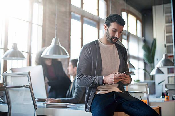 businessman checking the mobile phone sitting on his desk - gemak stockfoto's en -beelden