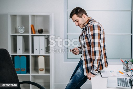 istock Businessman checking the mobile phone sitting on his desk 873062946