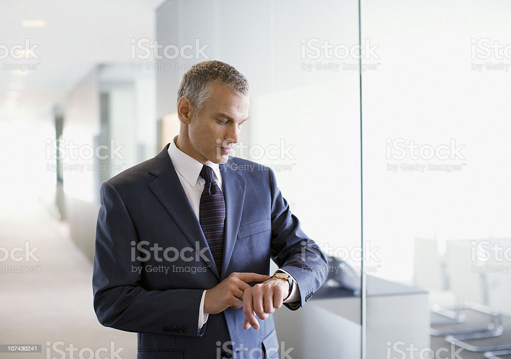 Businessman checking the time in office stock photo