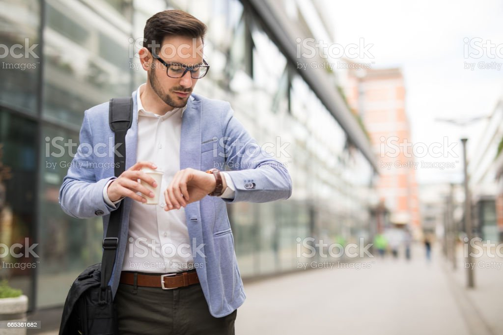 Businessman checking the time on his wrist watch stock photo