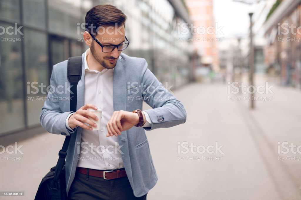Businessman checking the time on his wristwatch stock photo