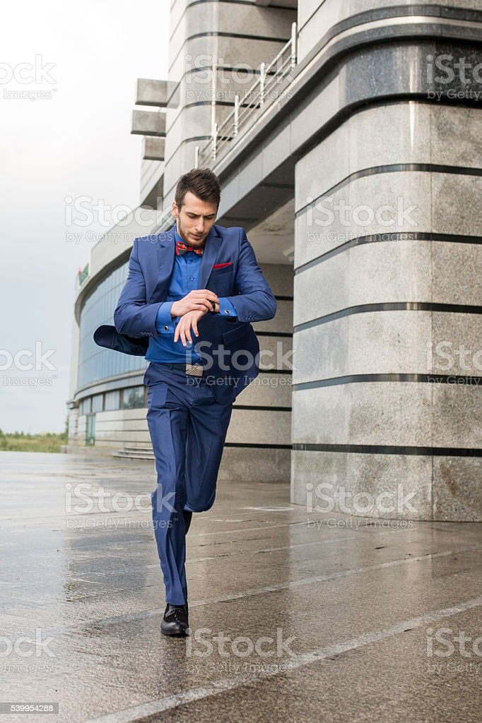 Businessman checking the time while running to work. stock photo