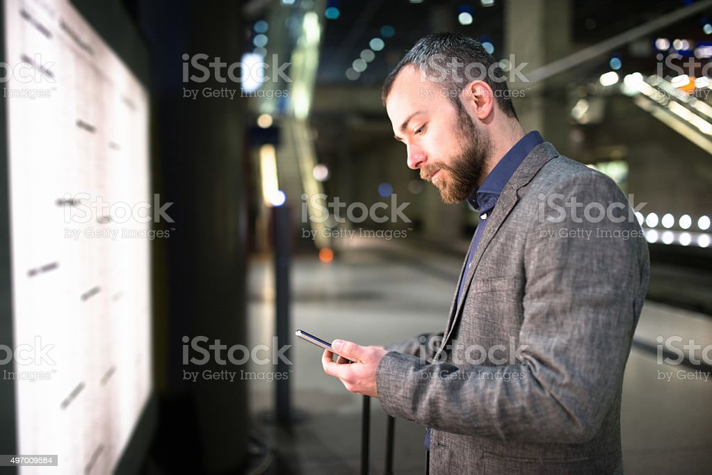 businessman checking the train time on the timetables stock photo