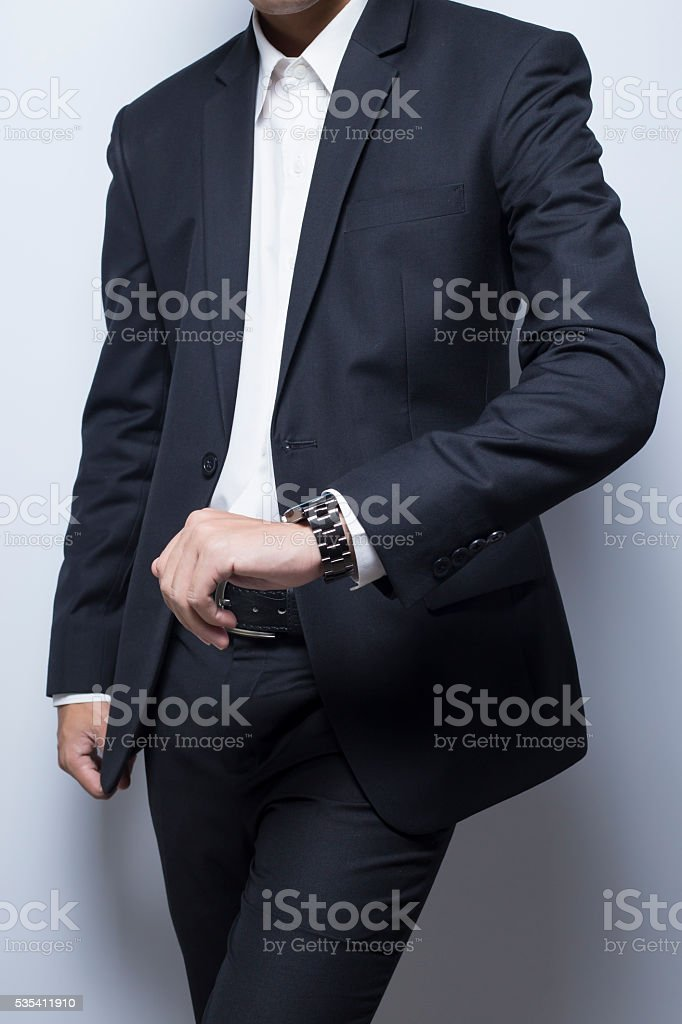 Businessman checking time from watch stock photo