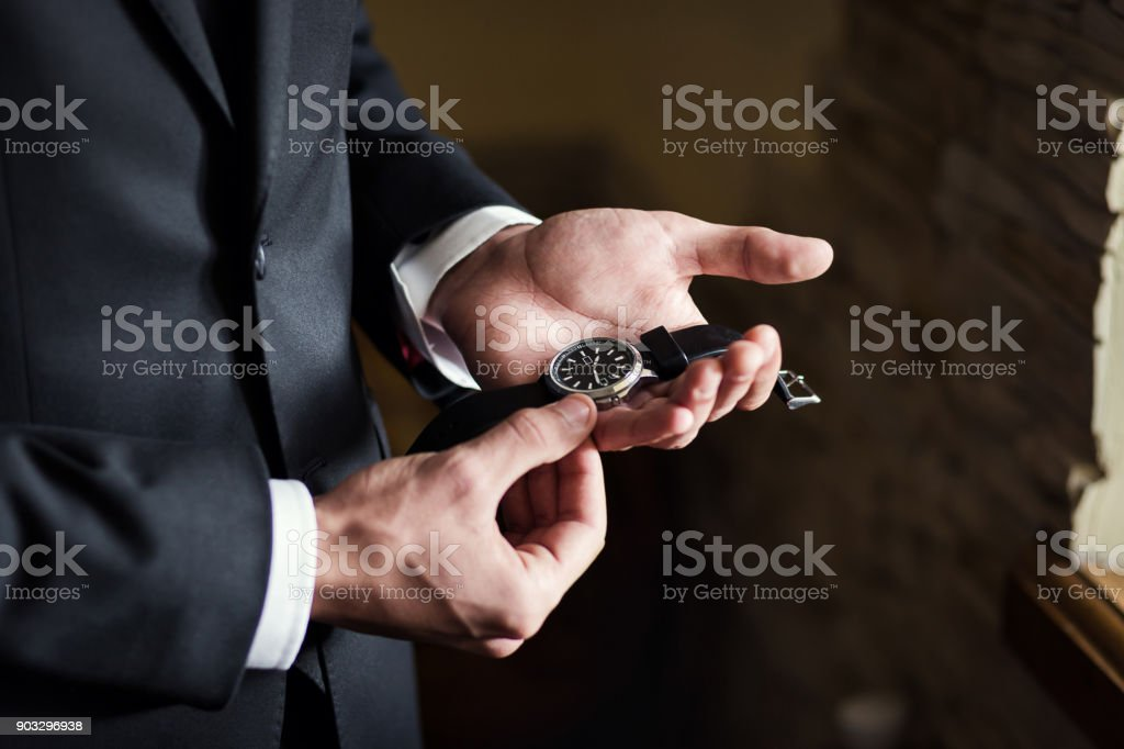 businessman checking time on his wrist watch, man putting clock on...
