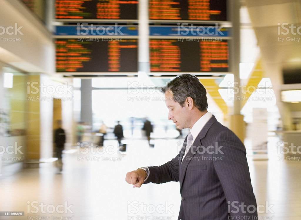 Businessman checking watch in airport royalty-free stock photo