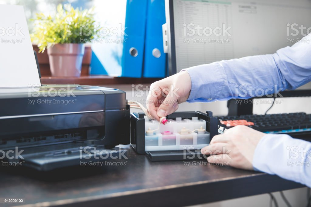 Businessman checks how much ink has been left in the printer's container stock photo