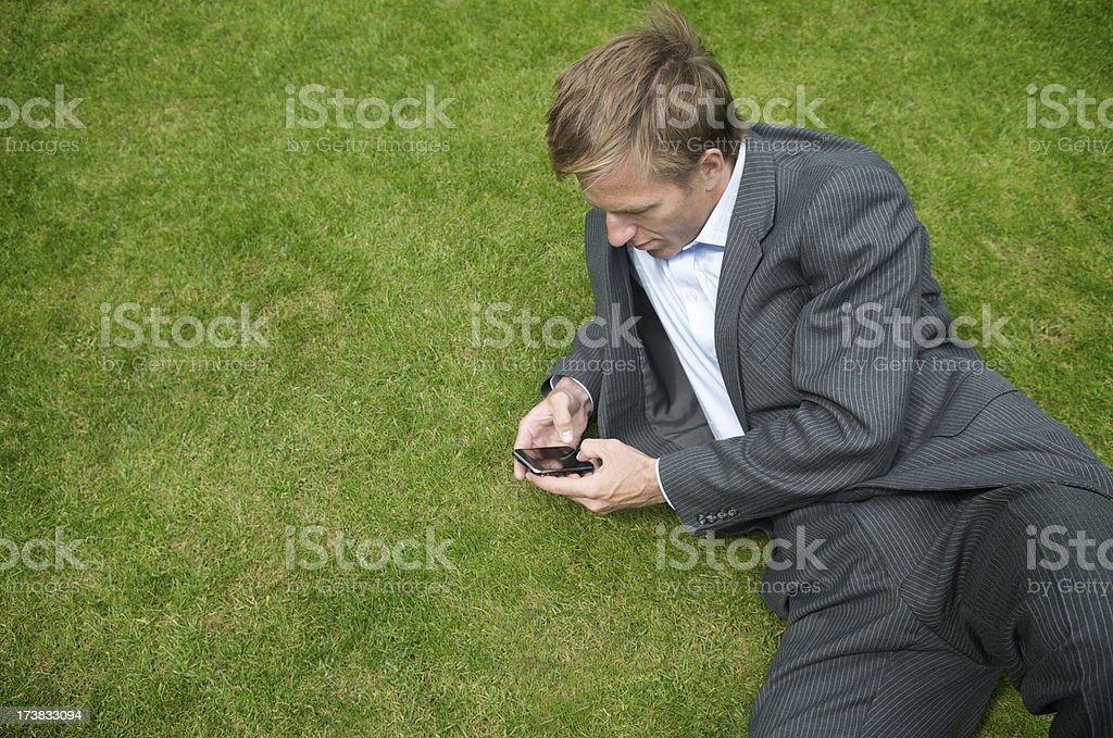 Businessman Checks Smartphone on Green Grass royalty-free stock photo