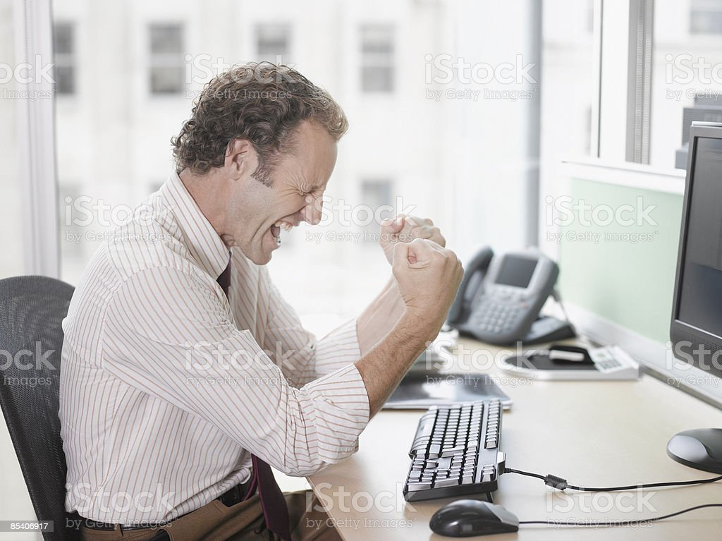 Businessman cheering at desk royalty-free stock photo