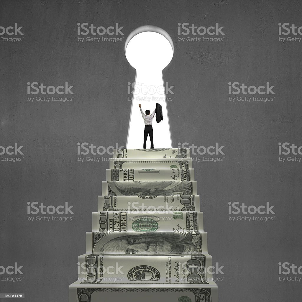 Businessman cheering in key shape hole stock photo