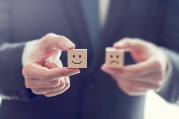 Geschäftsmann wählen Smiley Gesicht und verschwommen traurige Gesicht Symbol auf Holzwürfel, Service-Bewertung, Zufriedenheitskonzept. – Foto