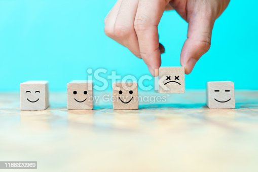 istock Businessman chooses a emoticon icons sadly on wooden block , Business bad teamwork concept 1188320969