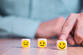 istock Businessman chooses a smile emoticon icons face happy symbol on wooden block , Services and Customer satisfaction survey concept 1171433470