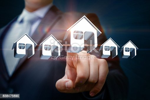 1023041738istockphoto Businessman chooses and clicks on a model home. 838475890