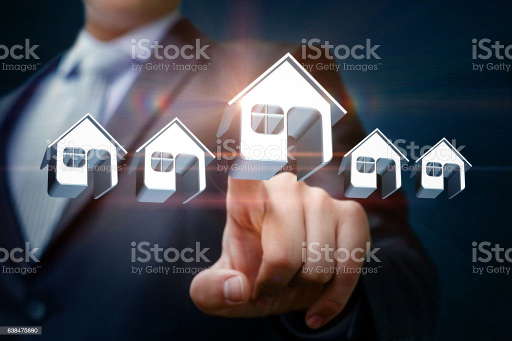 Businessman chooses and clicks on a model home. stock photo