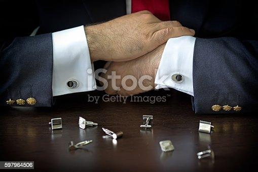 istock Businessman choosing cufflinks 597964506
