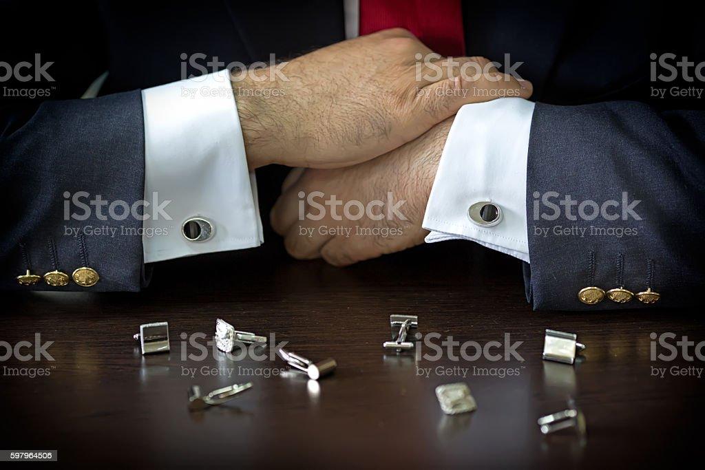 Businessman choosing cufflinks stock photo