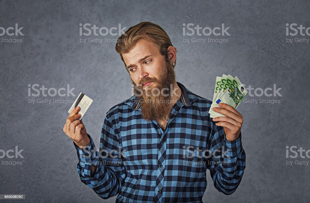 Businessman choosing holding showing plastic credit card or money cash euro banknotes bills, grey background stock photo