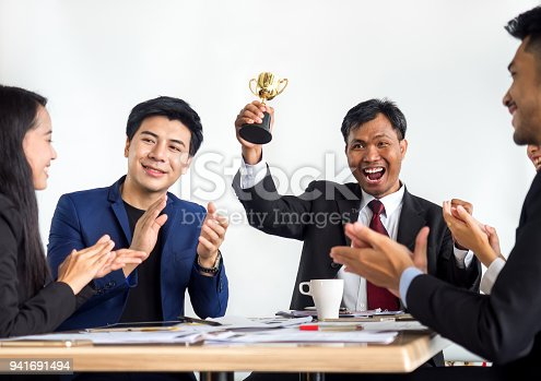 istock Businessman clapping hands with trophy, reward, winner, champion and successful for business 941691494