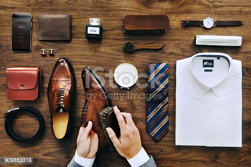 istock Businessman cleaning his shoes 909883316
