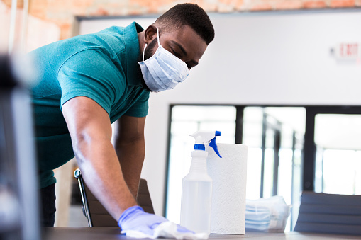 A serious mid adult man cleans a conference table in his office while wearing a protective face mask. He is cleaning the office before his colleagues arrive.