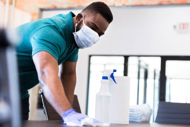 Businessman cleans conference table during COVID-19 pandemic stock photo