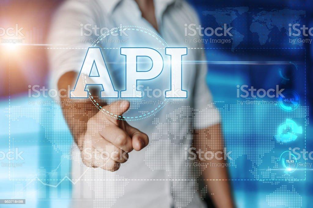 Businessman clicks on a virtual screen and selects 'API'. Blue background. Business concept. Mixed media - fotografia de stock