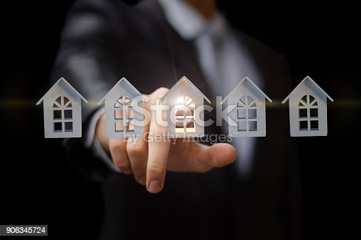 istock Businessman clicks on the house. 906345724