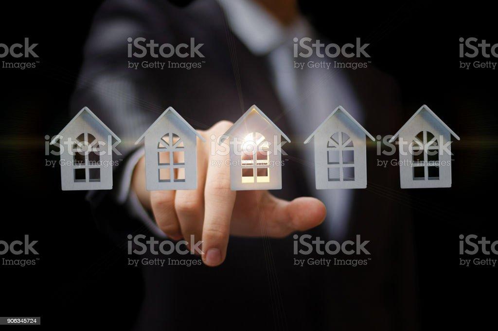 Businessman clicks on the house. stock photo