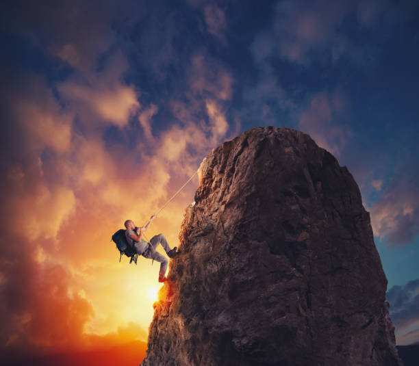 Businessman climb a mountain to get the flag. Achievement business goal and difficult career concept - foto stock