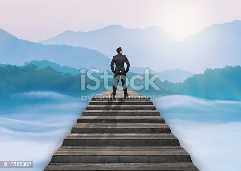 istock Businessman climbed on top of the stairs over the cityscape which can see beautiful scenary of mist with mountain range, Success business and Ambitions concept 812588302