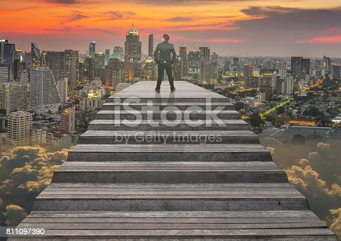 513121118 istock photo Businessman climbed on top of the stairs which can see top view of cityscape over the clouds background ,Success business and Ambitions concept 811097390