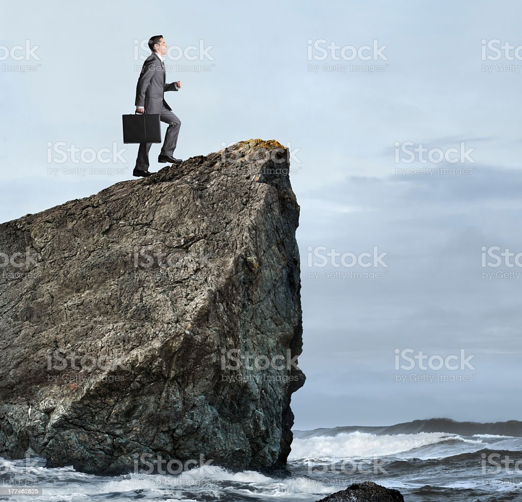 Businessman Climbing A Cliff Overlooking The Ocean royalty-free stock photo