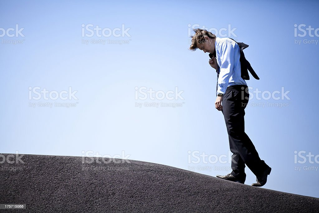 Businessman climbing a hill stock photo