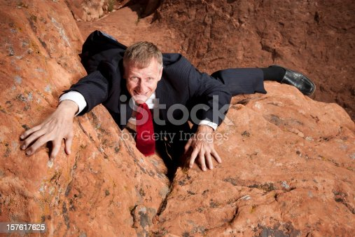 High angle view of a businessman in a suit and tie struggling to climb up a steep cliff.