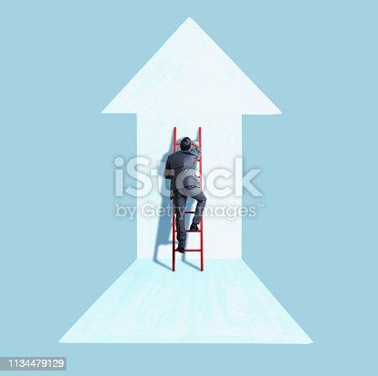 istock Businessman Climbing Ladder Following Direction of Arrow 1134479129