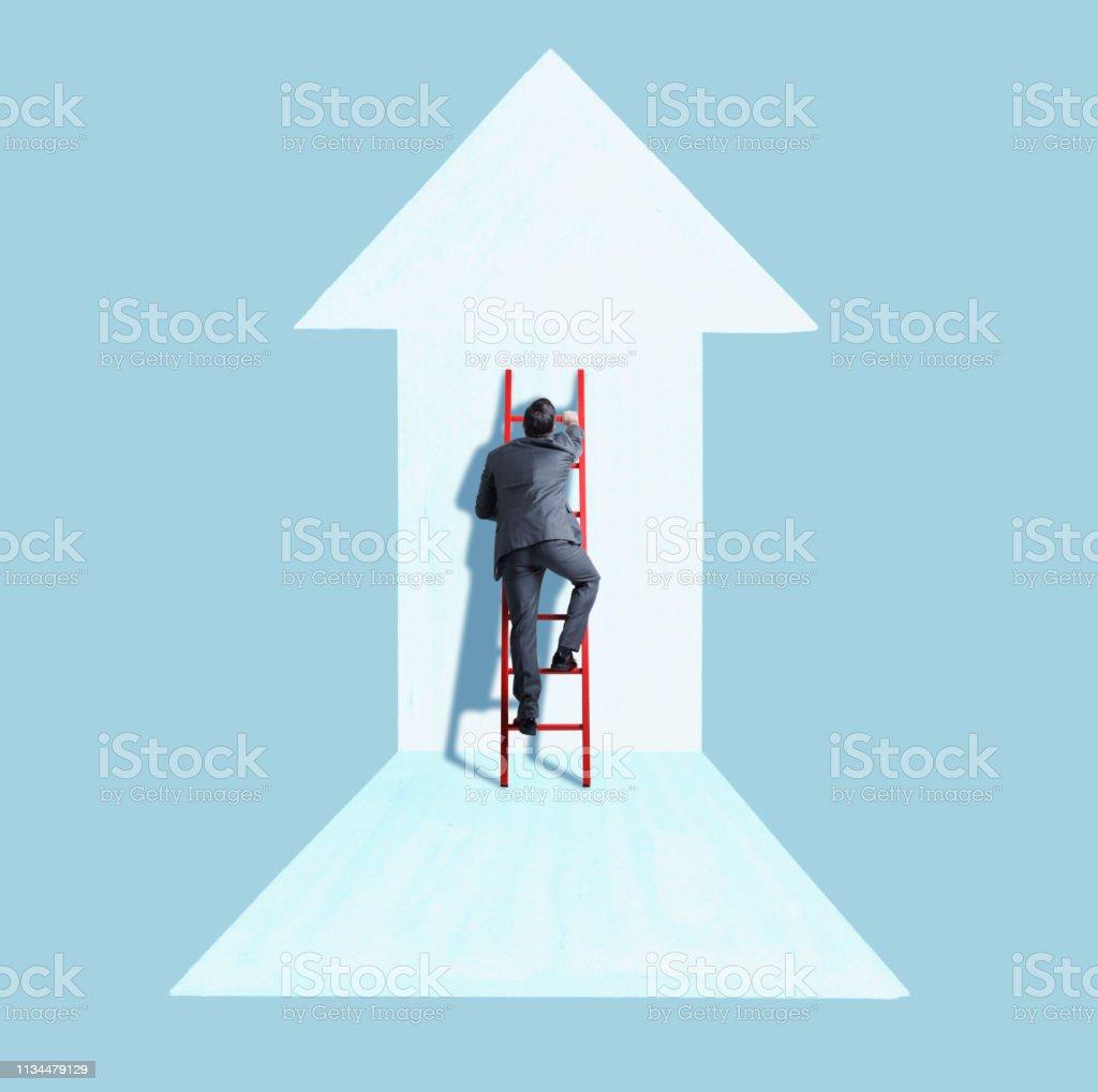 Businessman Climbing Ladder Following Direction of Arrow stock photo