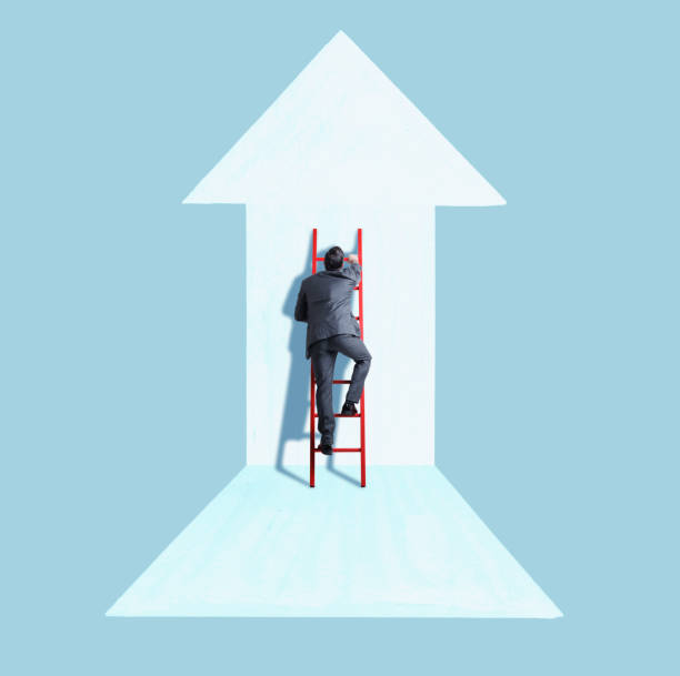 Businessman Climbing Ladder Following Direction of Arrow stock photo