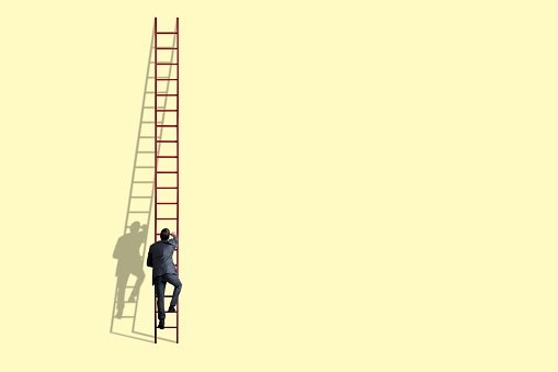 A businessman climbs a tall red ladder as his shadow against a light yelllow background.