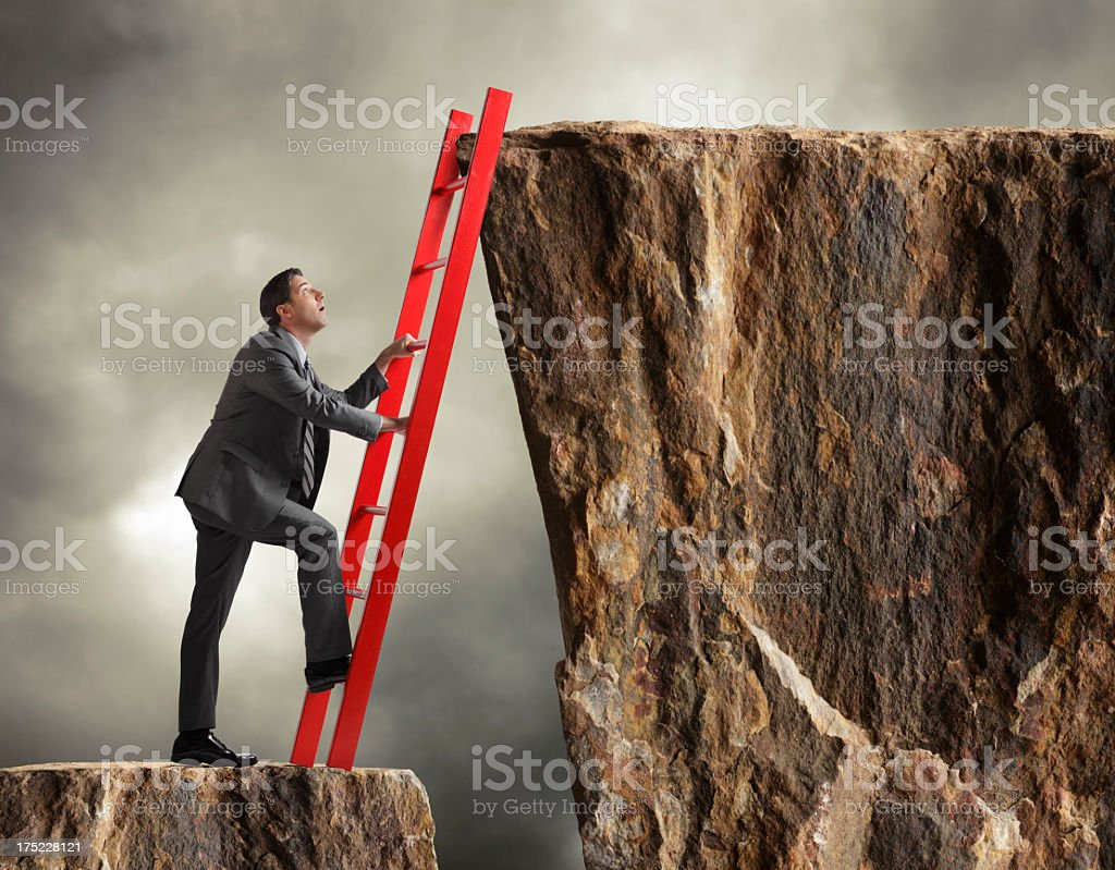 Businessman climbing ladder to get to higher level royalty-free stock photo