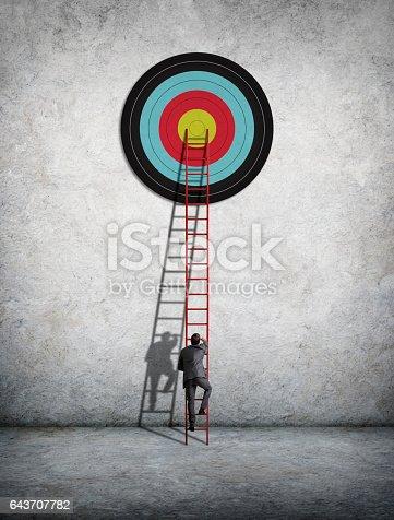 istock Businessman Climbing Ladder To Reach Target 643707782