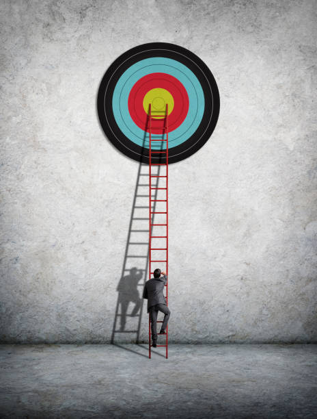 Businessman Climbing Ladder To Reach Target stock photo