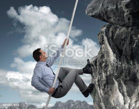 istock Businessman climbing mountain 454922915