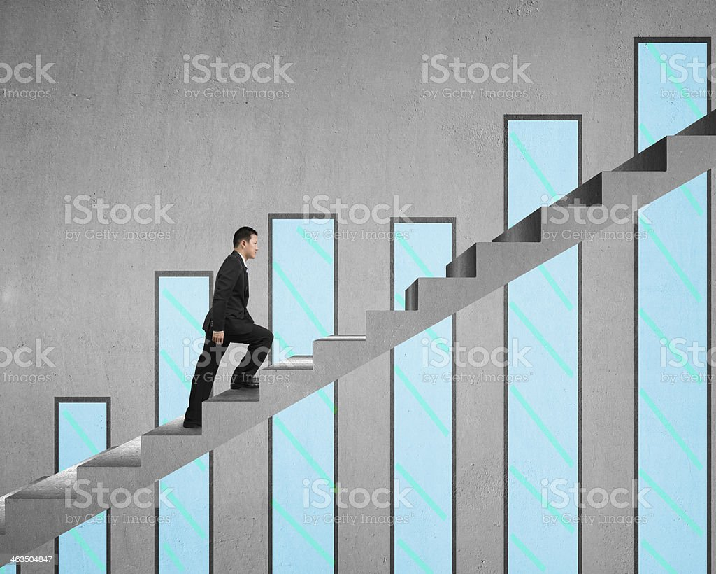 Businessman climbing on concrete stair with chart stock photo