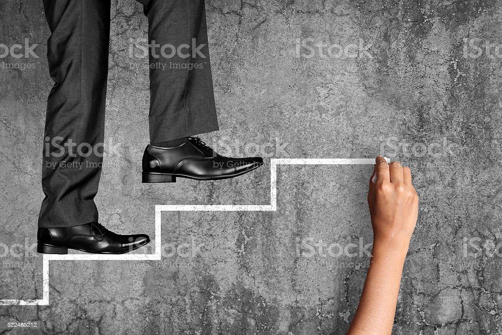 Businessman climbing on stairs stock photo