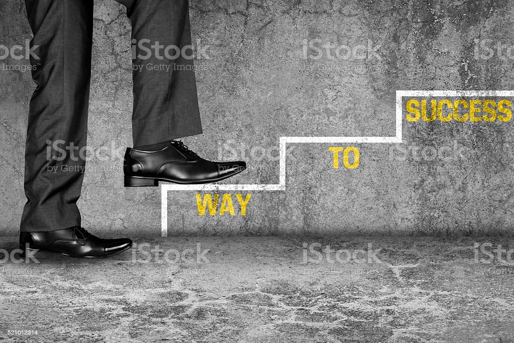 Businessman climbing on steps to achieve success stock photo