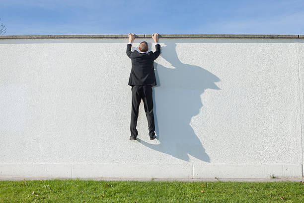 Businessman climbing over wall stock photo